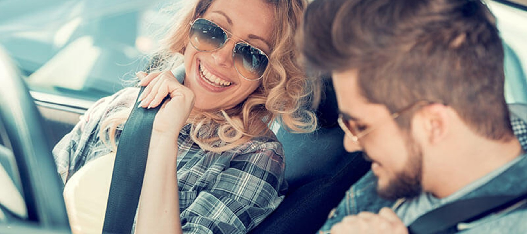 Two People Driving In Convertible Smiling