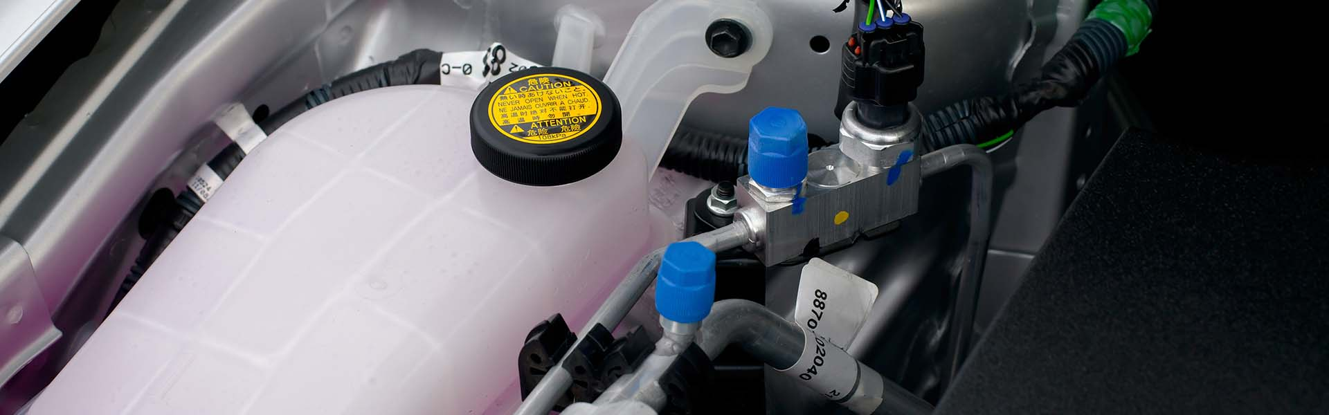 Coolant container in a car's engine bay